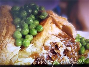 Подать пирог из слоеного теста с мясом вместе со свежим горошком