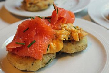 Подать картофельные оладьи с яичницей, кусочком семги, кресс-салатом