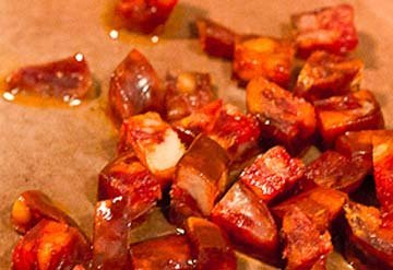 Нарезать колбасу и добавить в сковородку