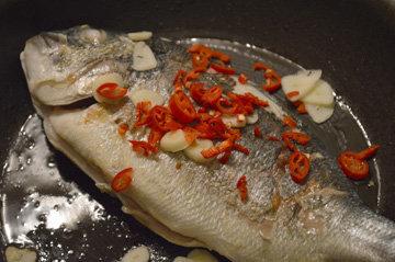 Положить чеснок между рыбой