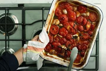 Выложить курицу в поддон с помидорами